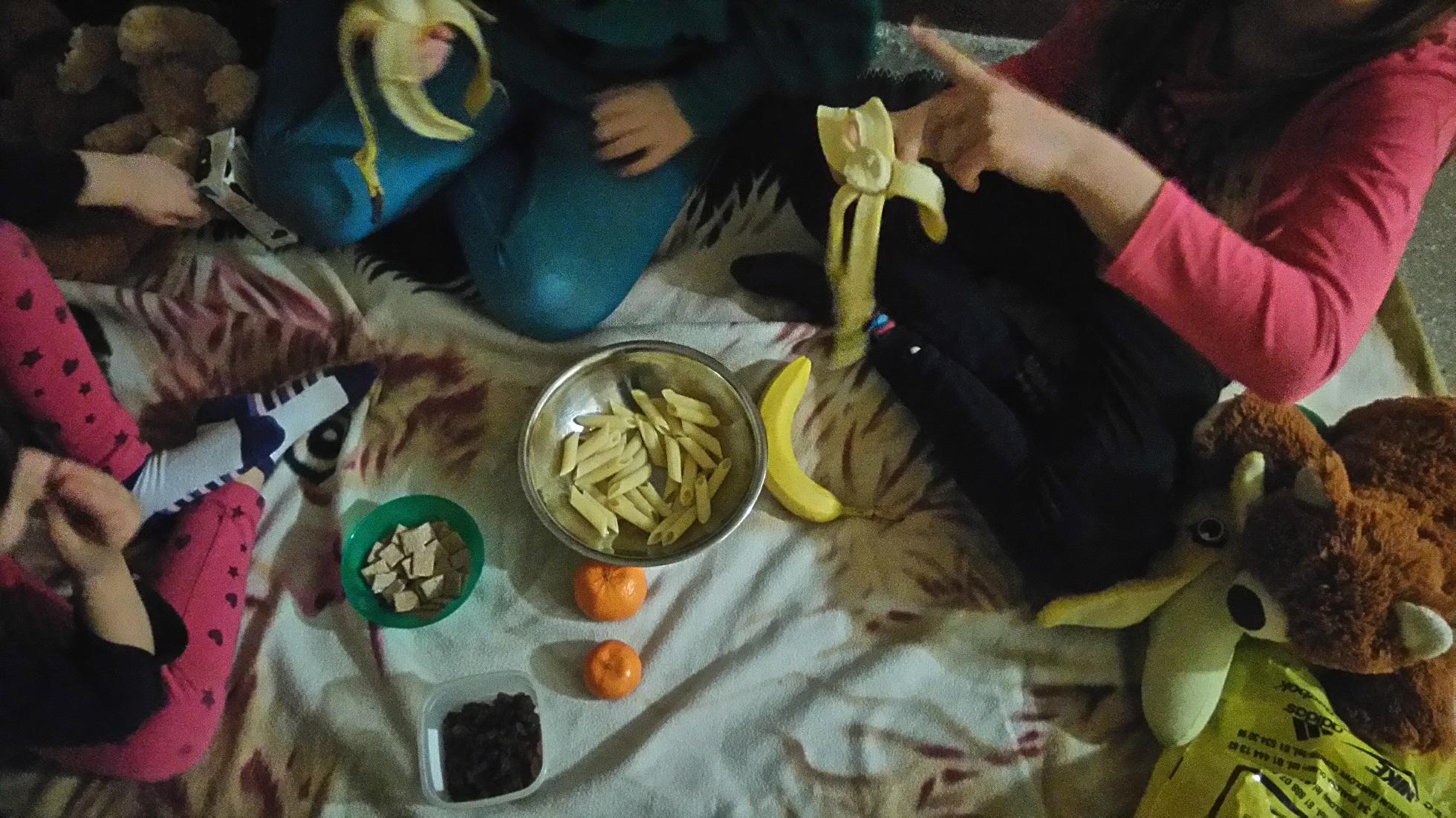 makaron, banany, mandarynki, płatki kukurydziane w zielonej misce leżą na piknikowym kocu, dzieci jedzące banany