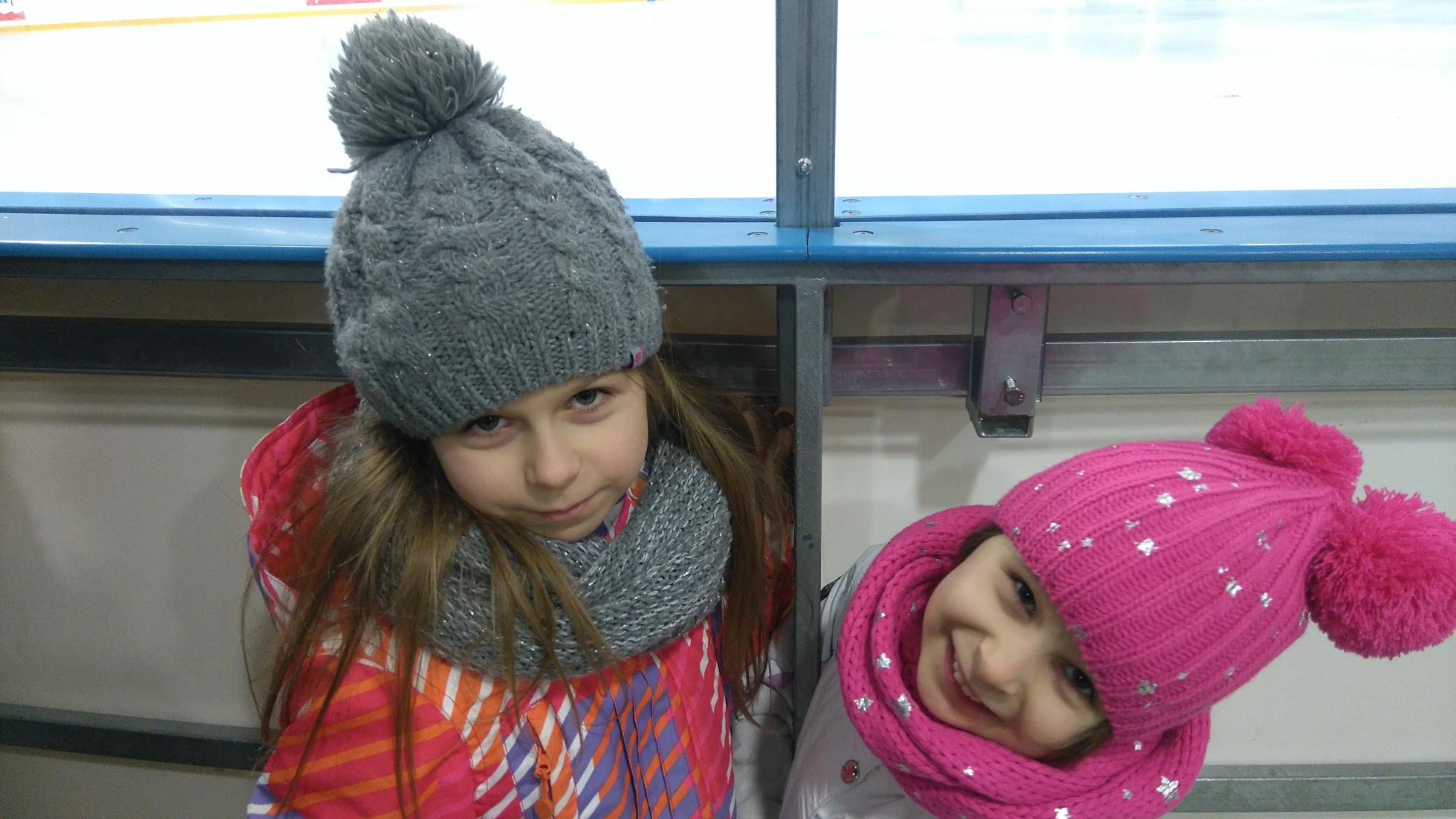 dwie dziewczynki w kurtkach, czapkach i szalikach