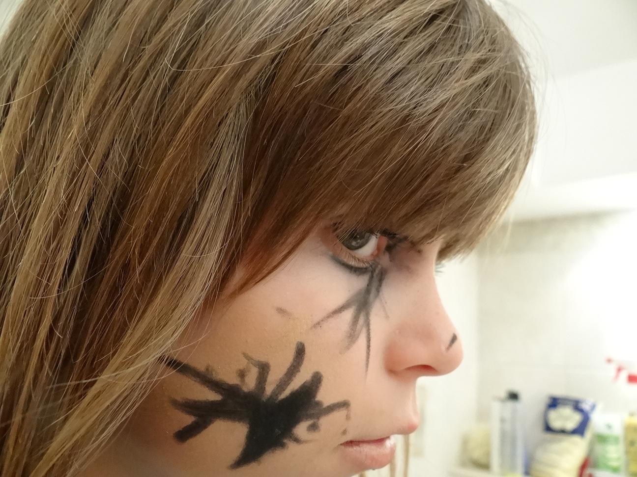 twarz dziewczynki pomalowana czarną kredką z profilu