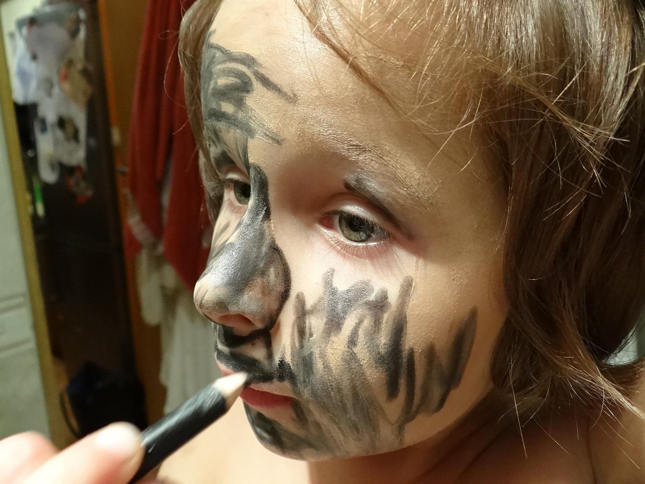 twarz dziewczynki pomalowana czarną kredką