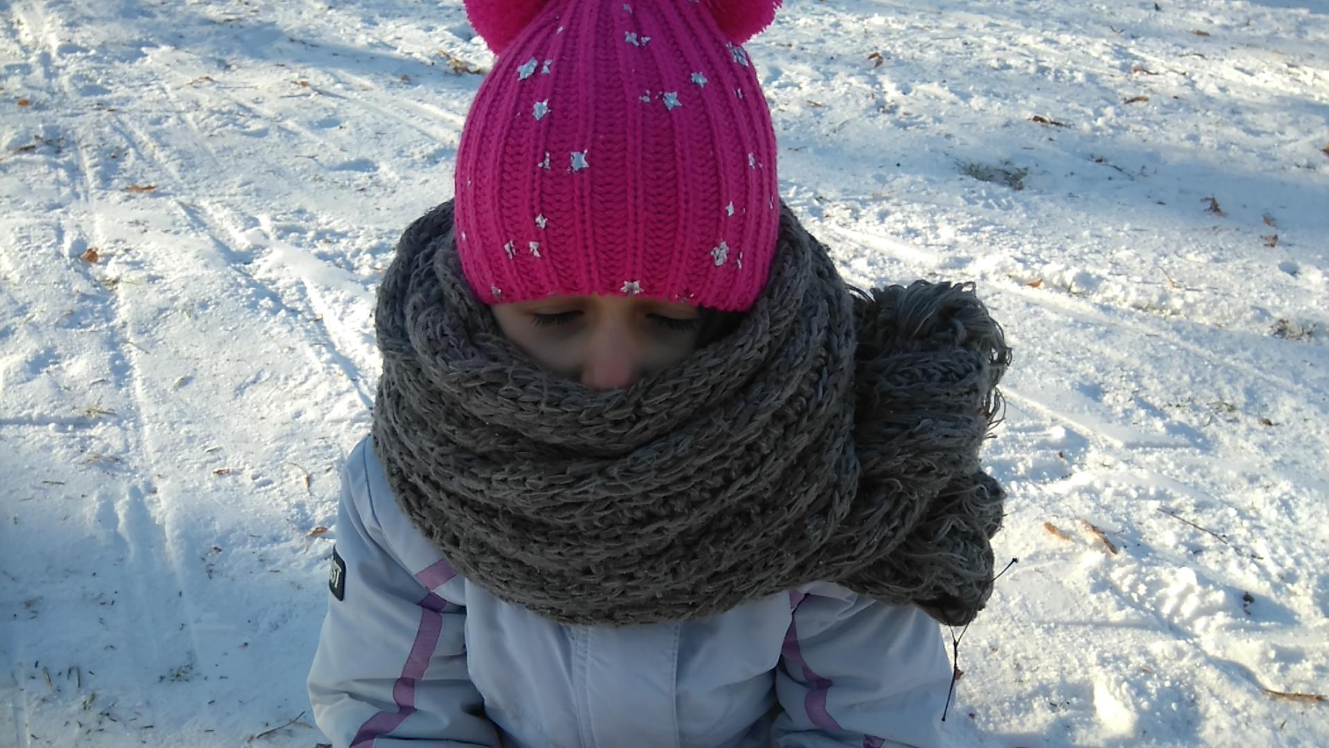 dziewczynka w kurtce i w czapce otulona szalikiem tak, że widać jej tylko oczy