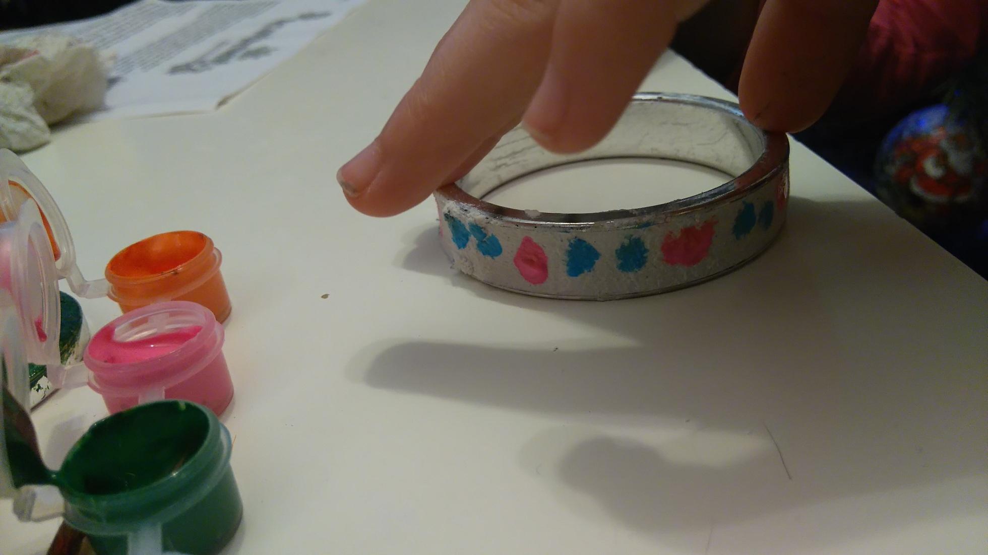 gipsowa bransoletka na w niebieskie i różowe kropki białym stole