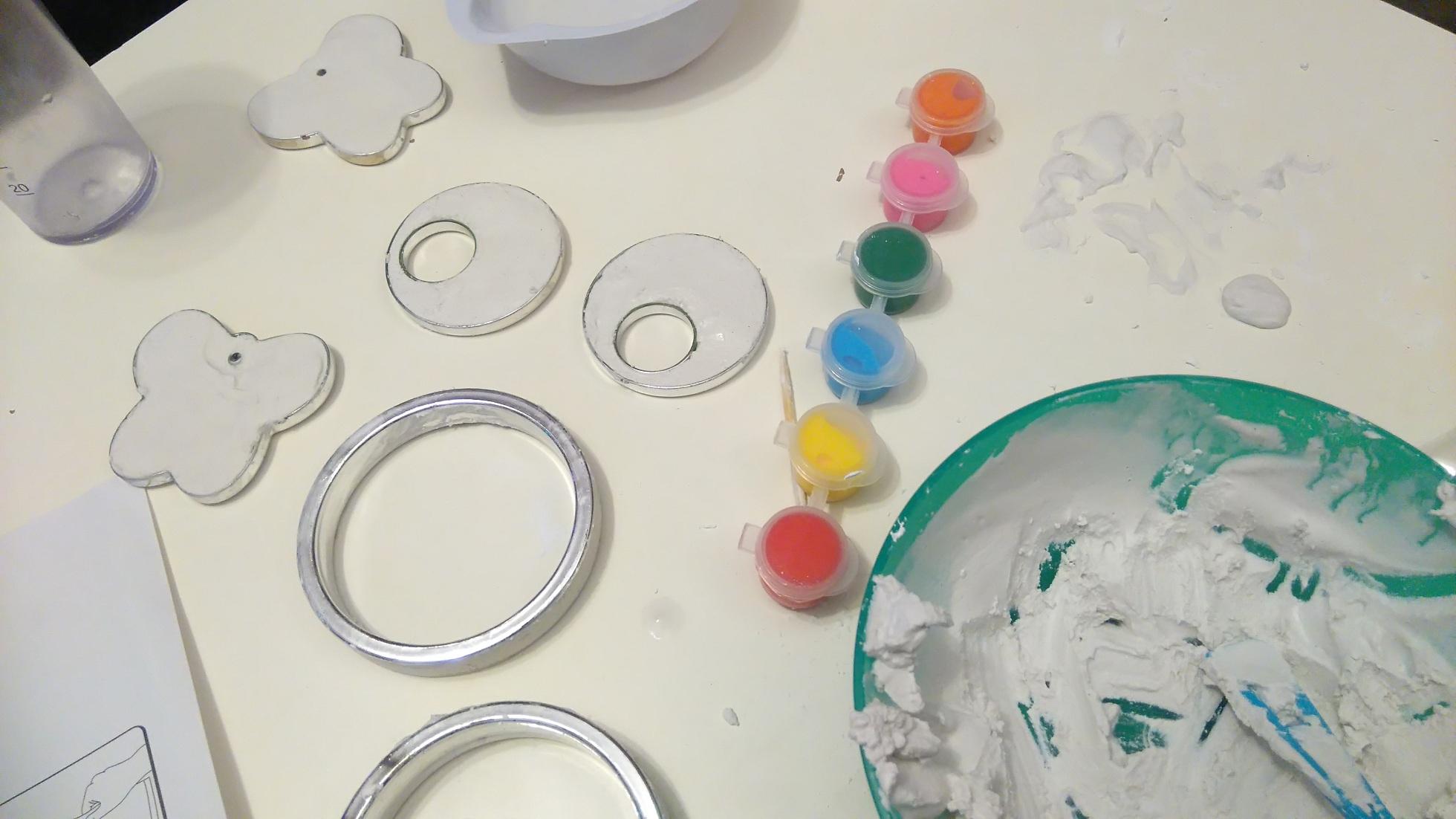 leżące na stole foremki wypełnione gipsem gotowe do malowania i farbki