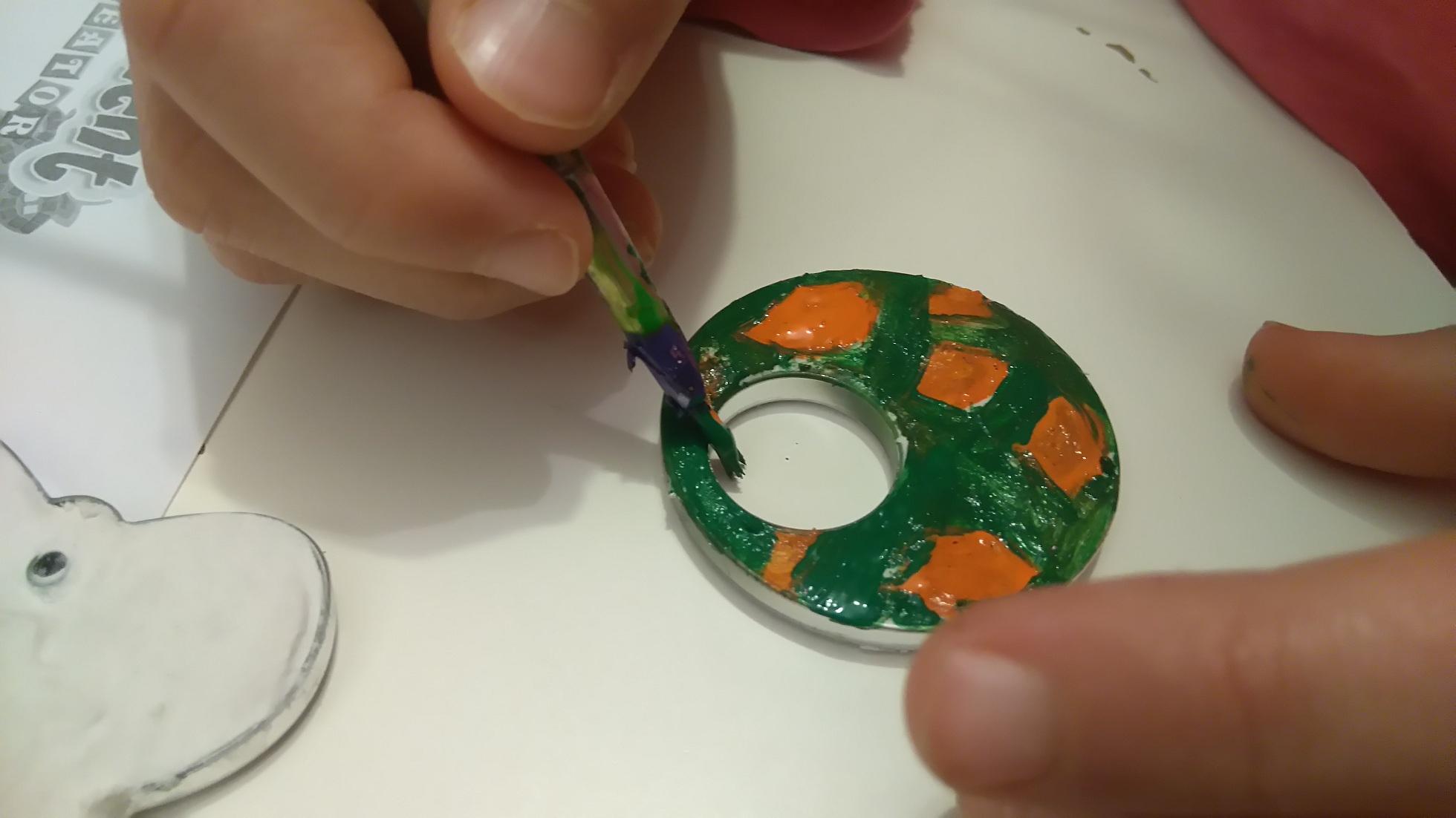 ozdabianie okrągłego gipsowego wisiorka przy użyciu pędzla i zielonej i pomarańczowej farbki