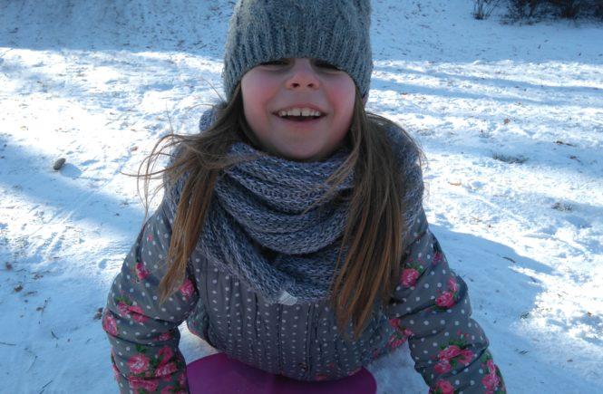 dzienka leży w kurtce na śniegu i się uśmiecha