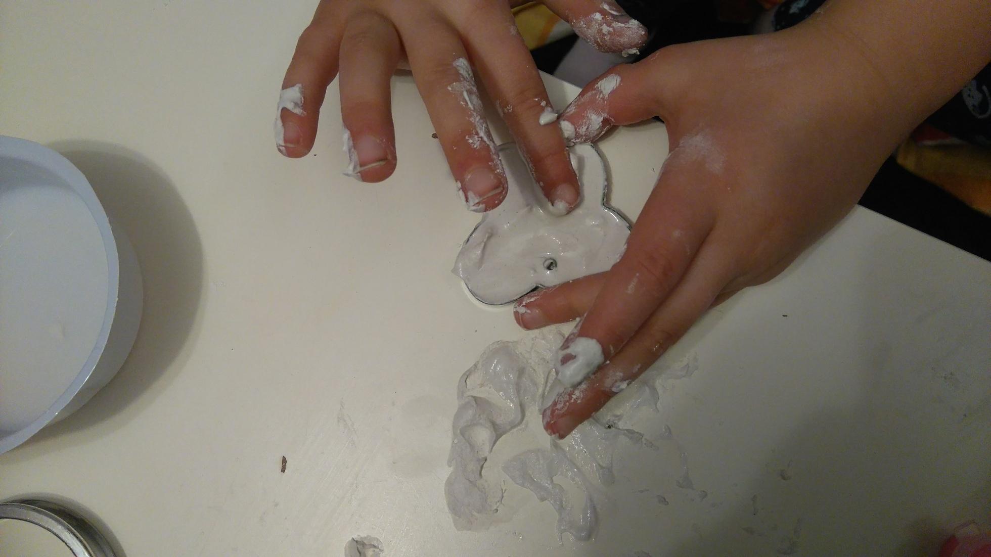 ręce wygładzające powierzchnię foremki wypełnionej gipsem