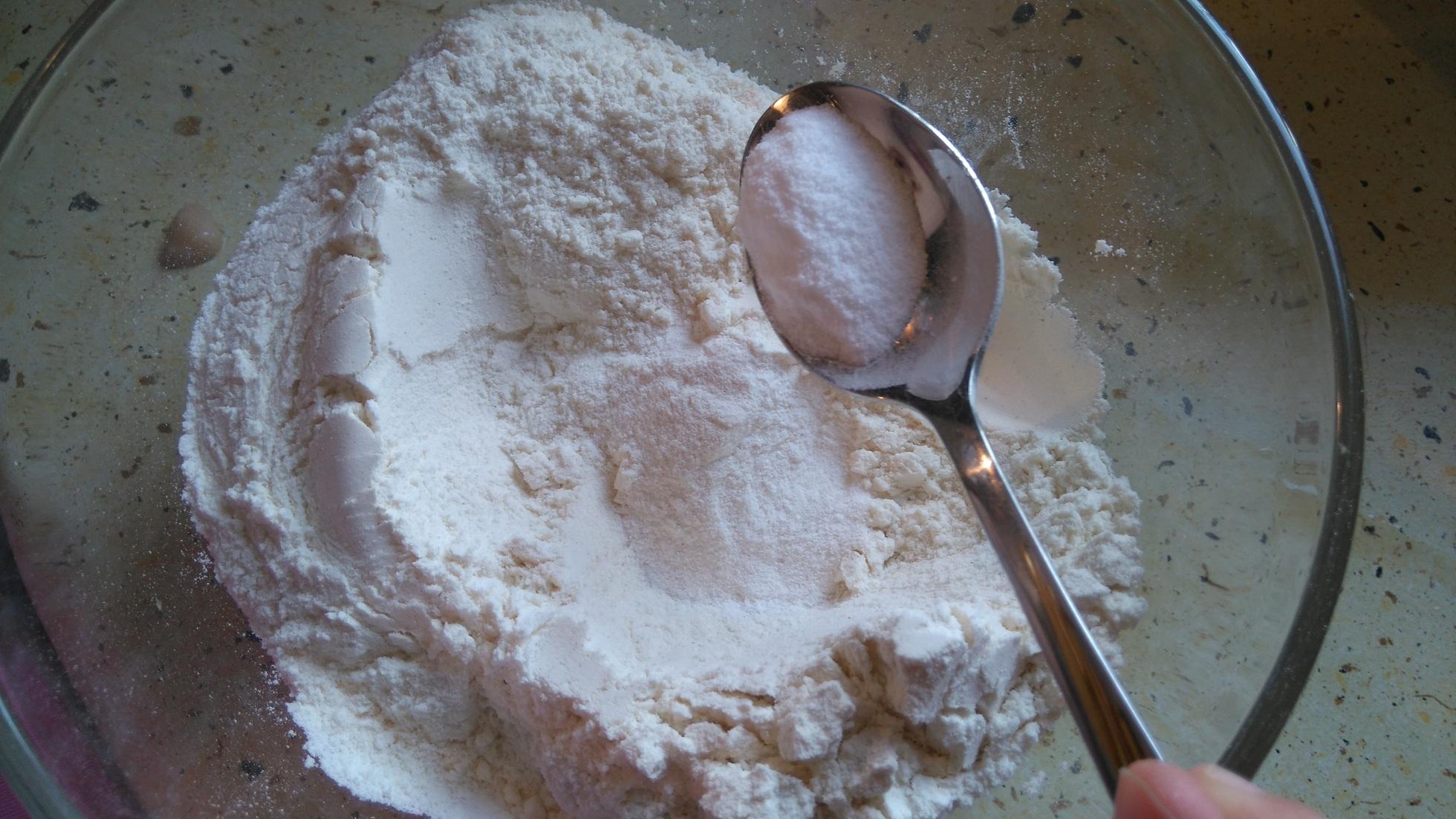łyżeczka z proszkiem do pieczenia na tle miski z mąką
