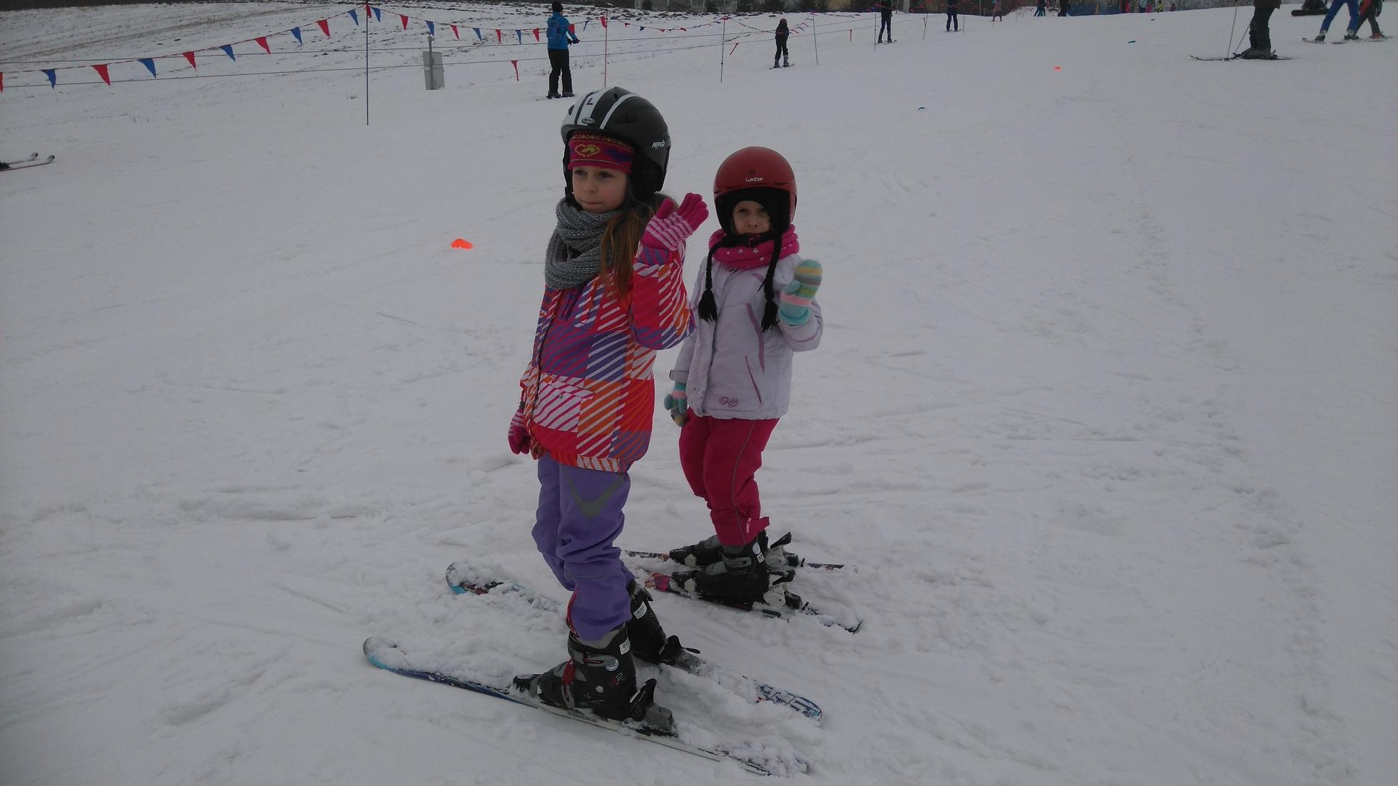 dwie dziewczynki w strojach narciarskich i nartach stoją na stoku