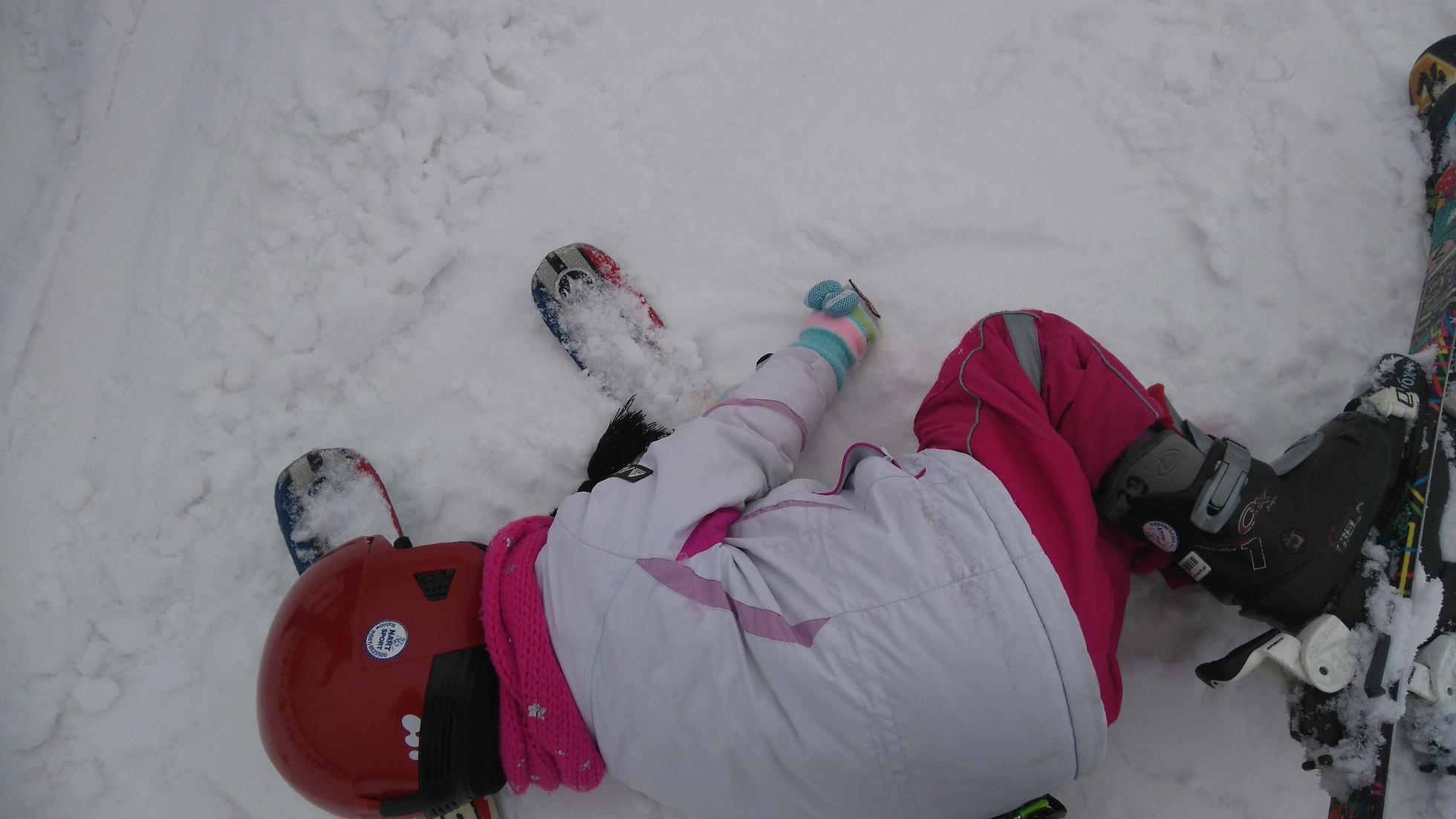dziecko leży na śniegu w stroju narciarskim