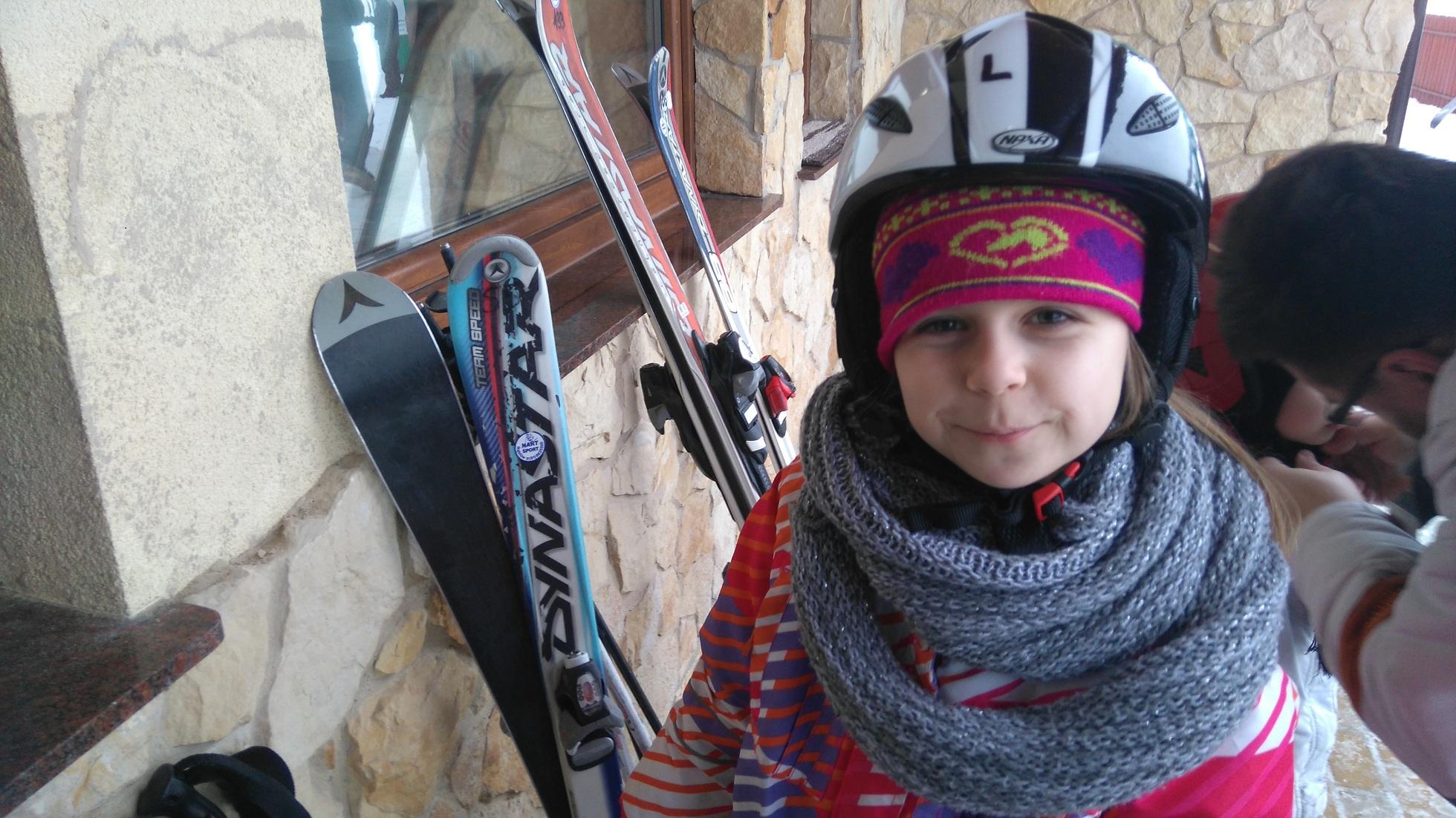 dziewczynka w stroju narciarskim, obok narty ooarte o ścianę budynku