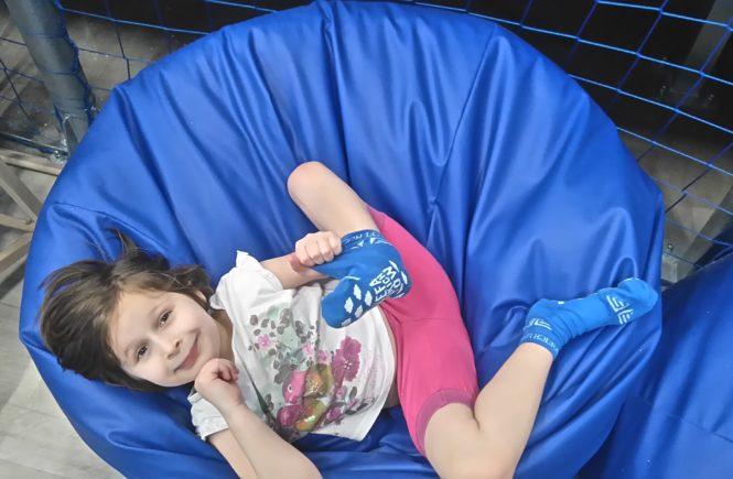 dziewczynka leży na niebieskim siedzisku