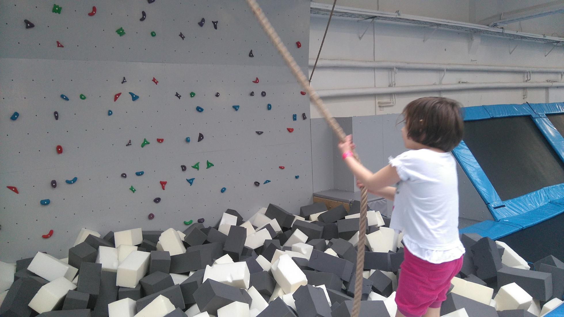 dziewczynka trzyma linę na tle ścianki wspinaczkowej i basenu z gąbkami
