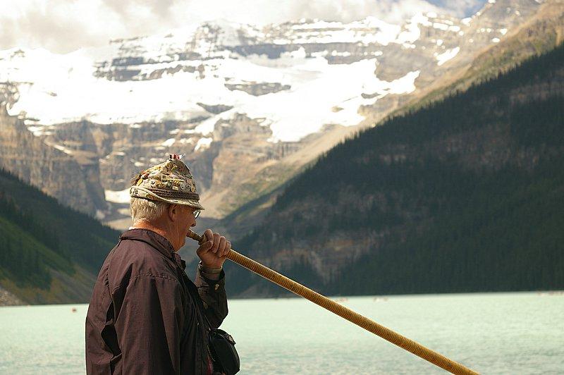 człowiek w górach trąbi