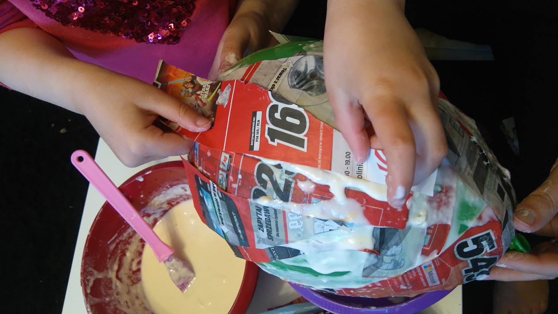 dziecięce rączki oklejają balon gazetami przy użyciu kleju z mąki i wody