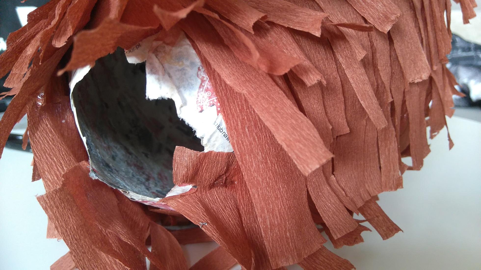 piniata z brązowymi frędzelkami z bibuły, widoczny otwór w piniacie