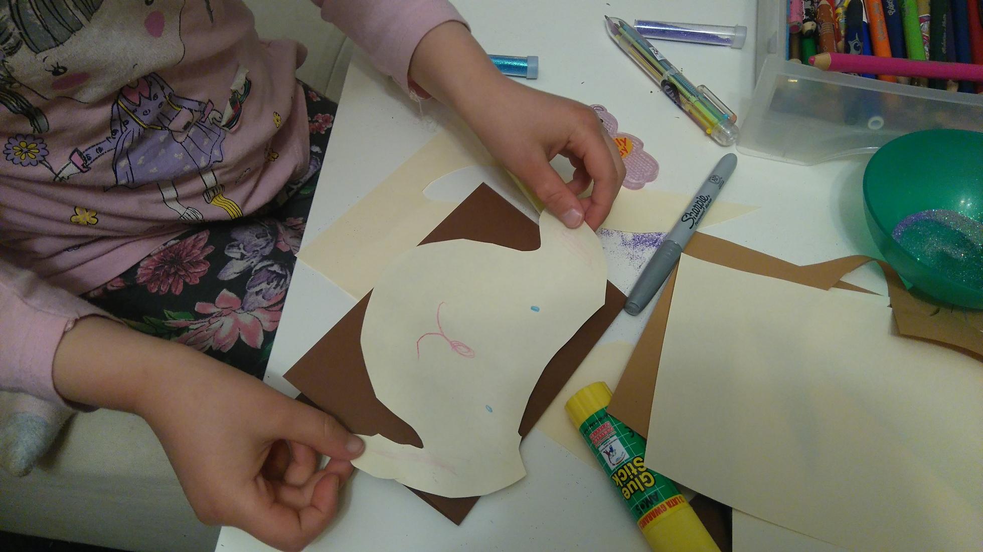 dziecko przykleja papierową głowę pieska do brazowego brystolu, wokoło akcesoria: klej, flamaster, dlugopis