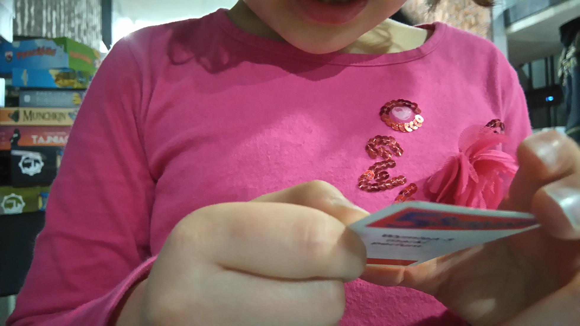 dziecko czyta napis na karcie do gry w 5 sekund, za nim leżą gry planszowe