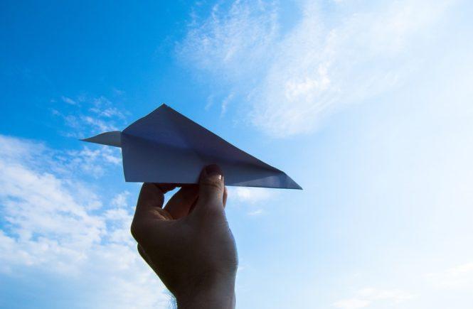 ręka trzymająca papierowy samolot na tle nieba