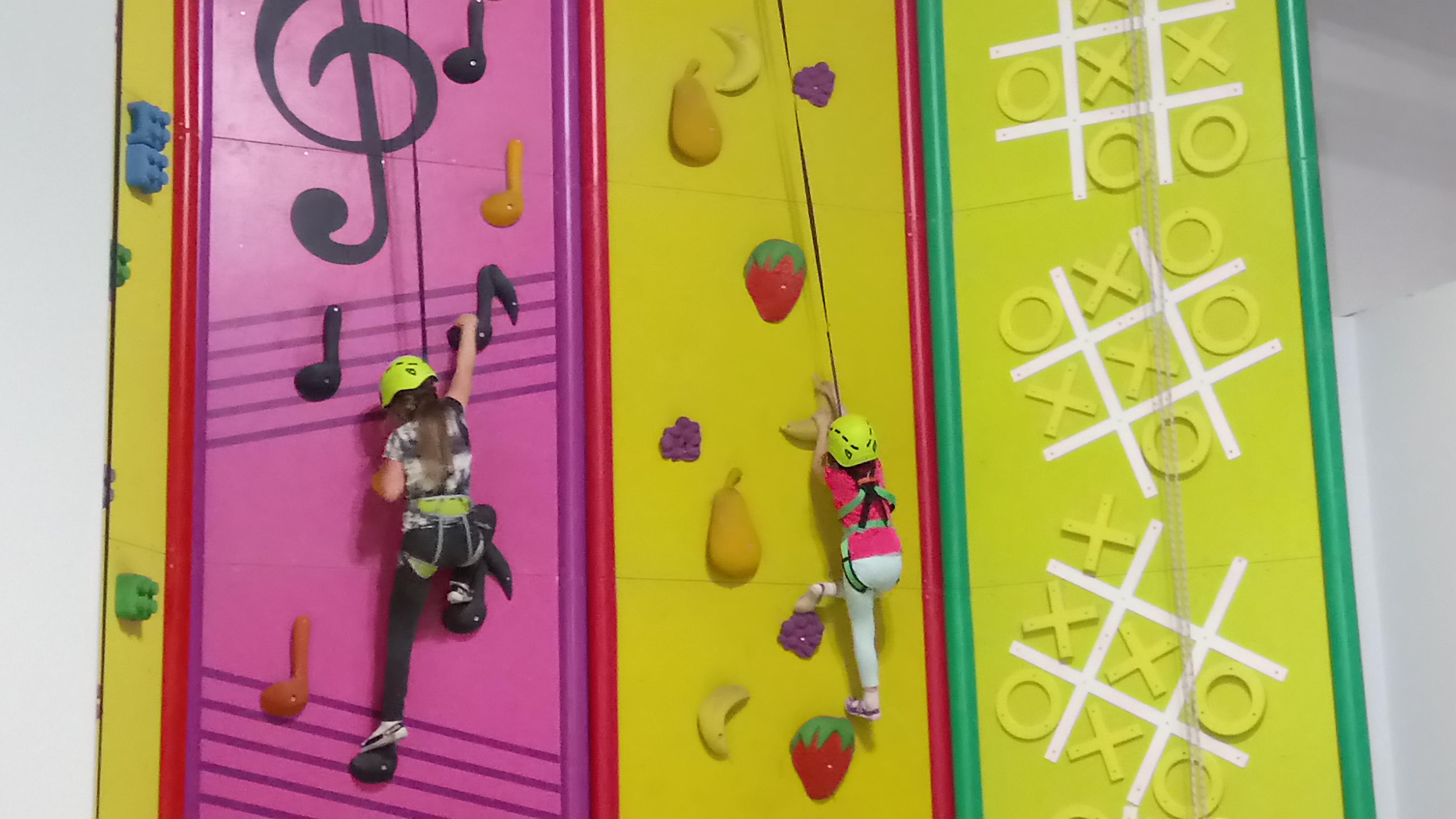 dwie dziewczynki wspinają się po kolorowych ściankach wspinaczkowych
