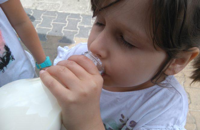 Dziewczynka pije mleko prosto z butelki