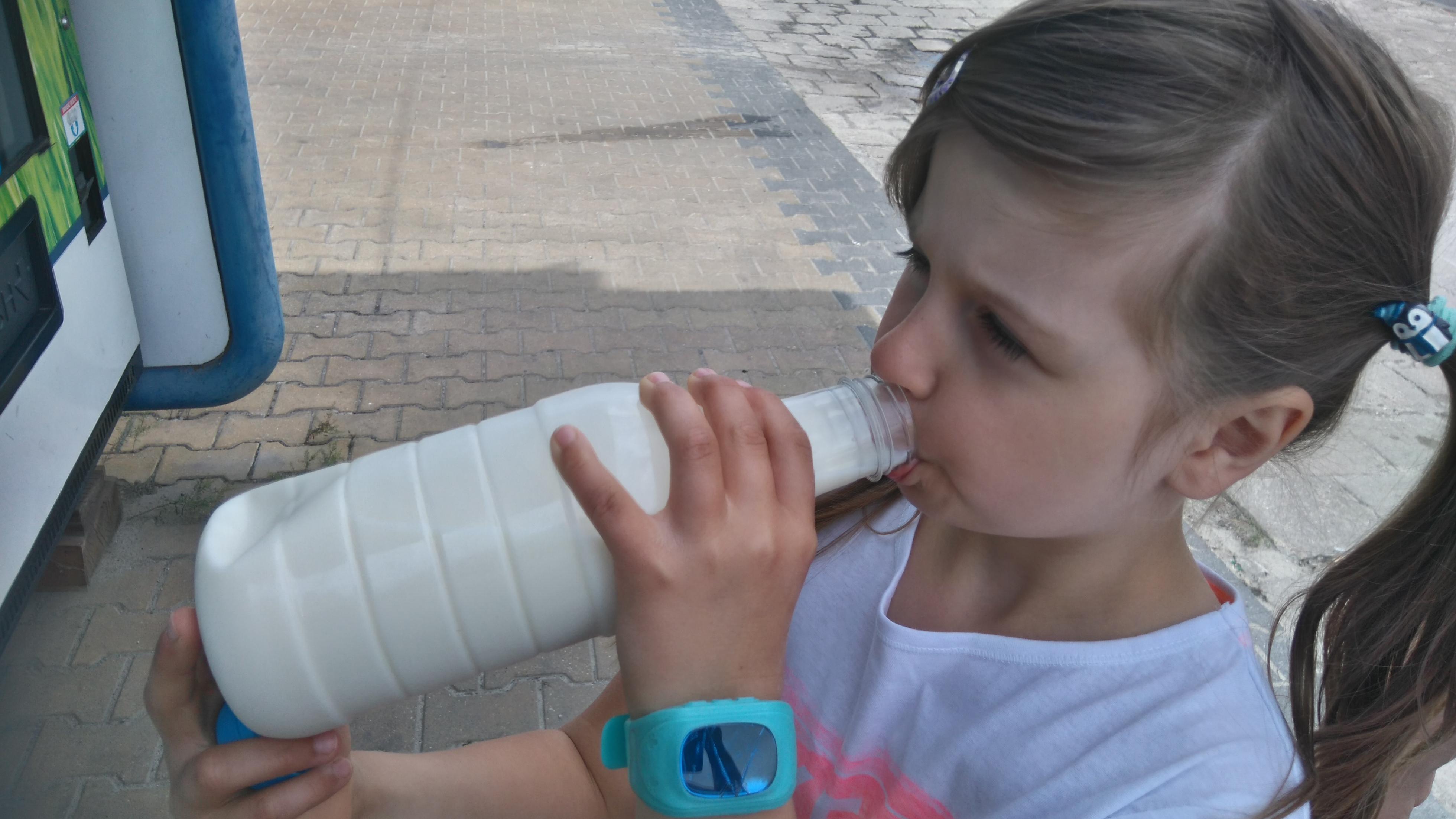 Dziewczynka pije mleko z mlekomatu