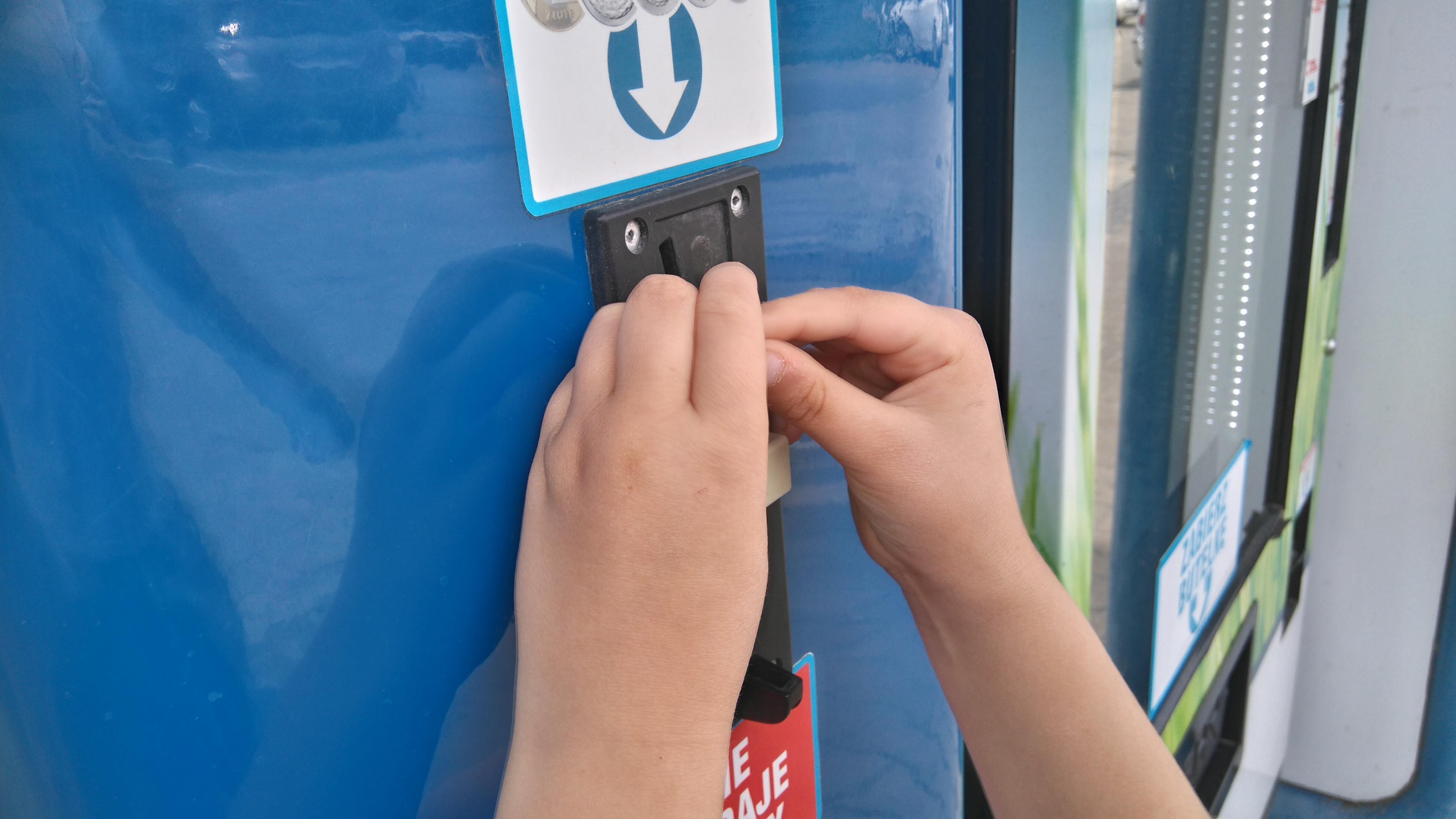 Dłonie dziecka wrzucają monety do automatu mlekiem