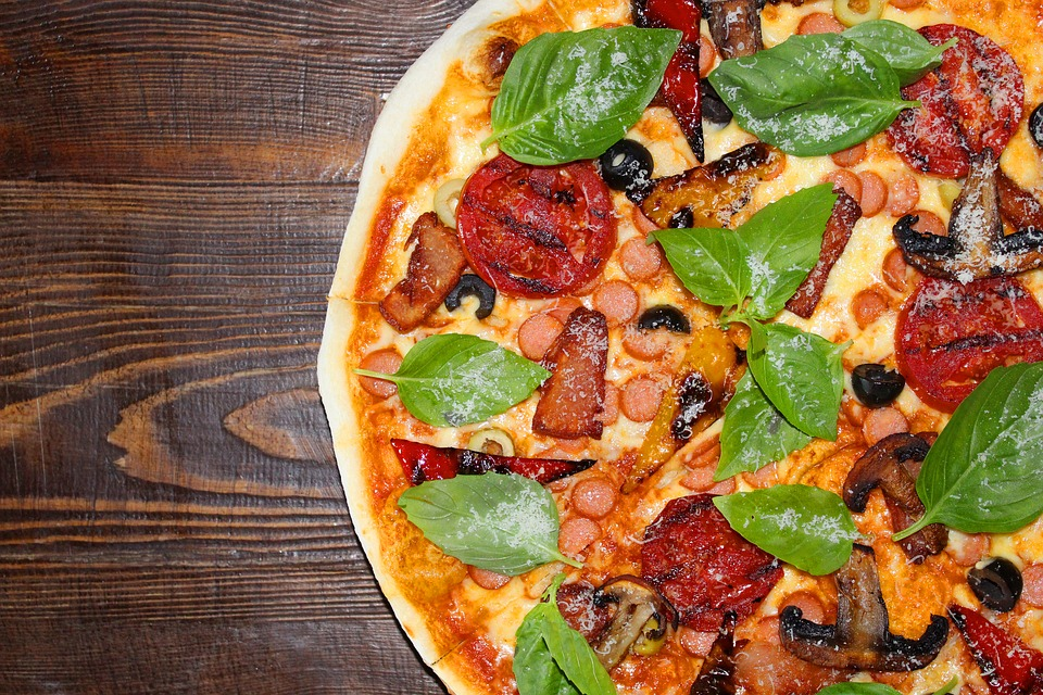 pizza na drewnianym blacie z różnymi składnikami