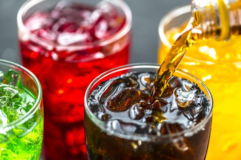 brązowa coca cola nalewana do szklanki z lodem, obok w szklankach napoje w kolorze żółtym i czerwonym